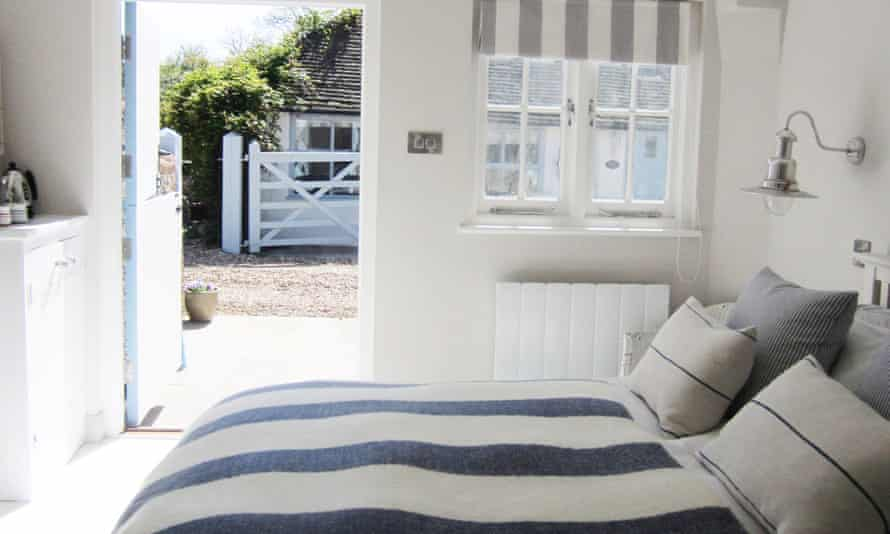 A bed with blue and white striped bedding and an open door leading outside