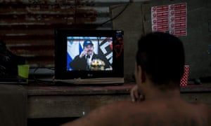 A man watches a television as President Daniel Ortega appears during a broadcast in Managua, Nicaragua, on Wednesday. He boasted that Nicaraguans 'haven't stopped working'.