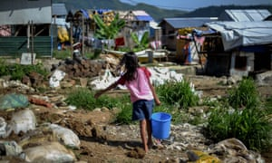 A girl makes her way home after fetching water at a coastal village in Tacloban, Leyte province.