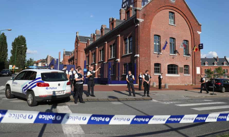 Officers secure the area around a police building in Charleroi, Belgium.