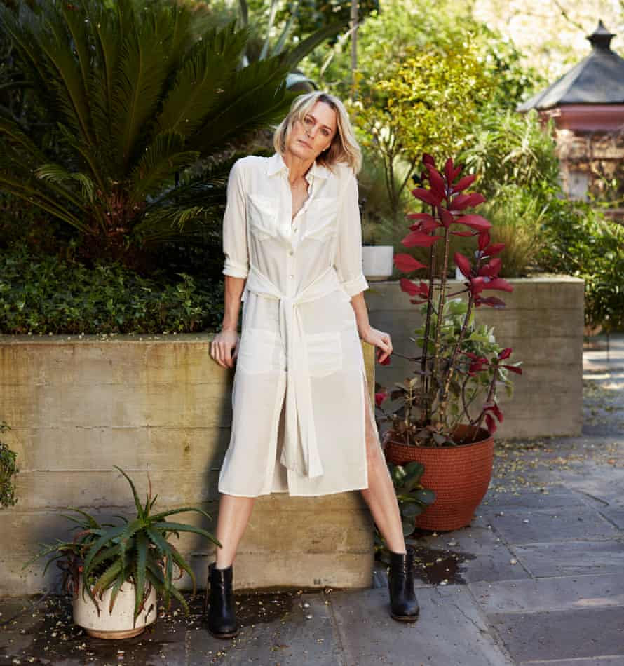 Robin Wright standing in a garden in a white dress