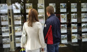 Young people looking in estate agent window