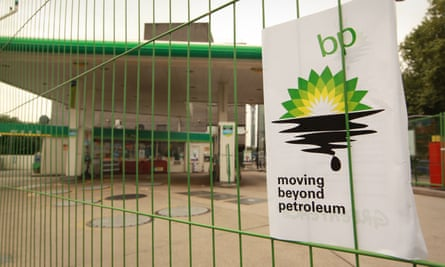 A Greenpeace poster displaying a leaking oil logo on closed a BP petrol station in Camden, London