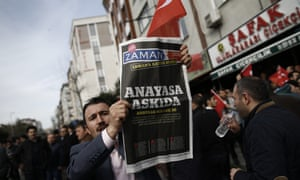 A man holding a copy of the Zaman newspaper in Istanbul with the headline 'Constitution suspended'.