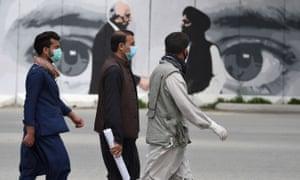 Kabul residents pass a mural of the US envoy Zalmay Khalilzad, left, and head of the Taliban peace delegation, Mullah Abdul Ghani Baradar.