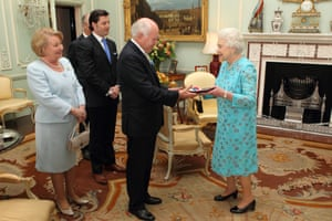 The monarch presents the Order of Merit to the former prime minister John Howard at Buckingham Palace in 2012, as his wife Janette looks on.