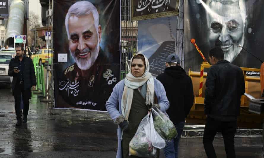 Pedestrians walk past banners of Iranian general Qassem Suleimani in Tehran