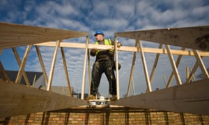 A worker helps construct housing on a Bellway building site