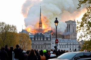 Seen from across the river Seine, smoke and flames rise at the landmark Notre Dame Cathedral in central Paris