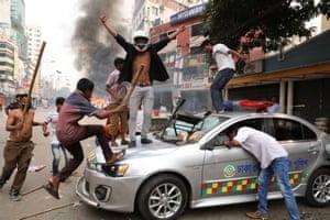 Dhaka, Bangladesh. Bangladesh Nationalist Party activists vandalise a police car during clashes on the streets