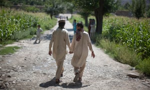 Afghan boys holds hands while leaving their school in the village of Asmar, Kunar province, Afghanistan.