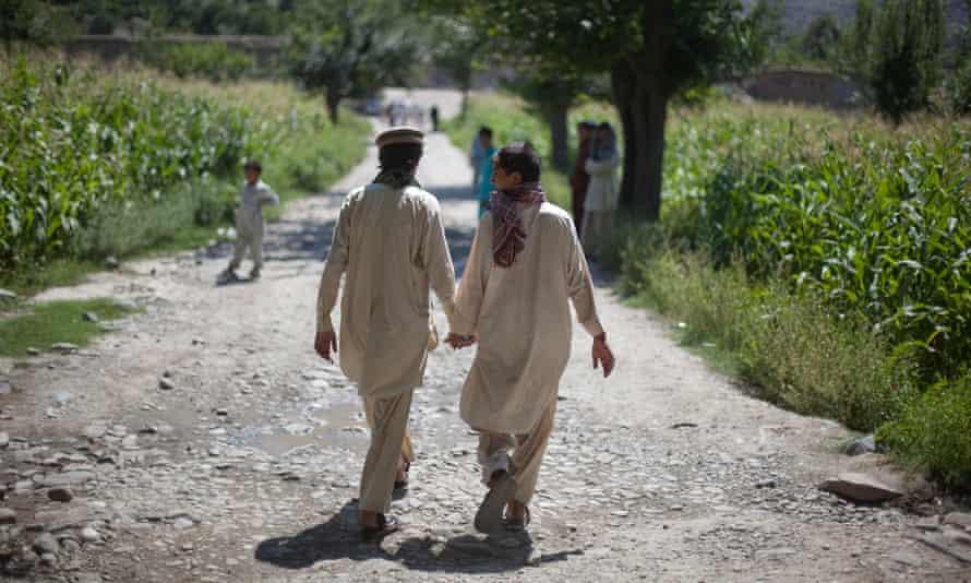 Afghan boys holds hands while leaving their school in the village of Asmar, Kunar province, Afghanistan.
