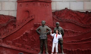 A girl takes a selfie with statues depicting late Chinese chairman Mao Zedong and former general Zhu De during the War of Resistance against Japan