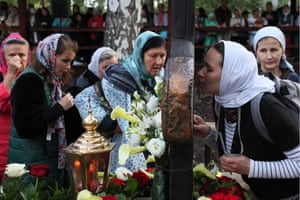 Sverdlovsk, Russia. A woman kisses a cross during a religious procession in memory of Emperor Nicholas II of Russia and his family, who were executed on this date in 1918