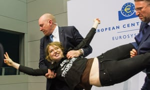 """A protester who jumped on top of ECB president Mario Draghi's desk during a news conference at the European Central Bank is detained by security. Her shirt reads """"End the ECB Dick-tatorship""""."""