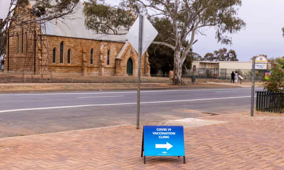 Sign with a Covid clinic sign with sandstone church in the background