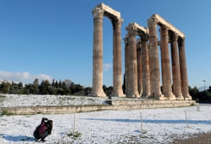 A young girl takes pictures of a snowy Temple of Olympian Zeus in Athens, Greece