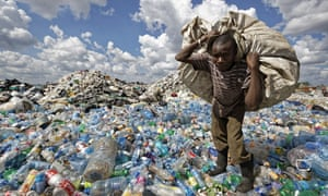 A man walks on a mountain of plastic bottles, carrying a sack of them to be sold for recycling, at the dump in the Dandora slum of Nairobi, Kenya.
