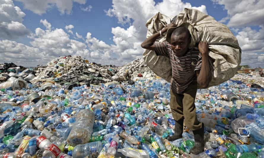 A man walks carries a sack of bottles to be sold for recycling after weighing them at the dump in the Dandora slum of Nairobi, Kenya.