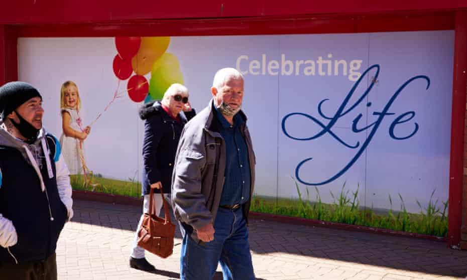 Pedestrians pass a billboard