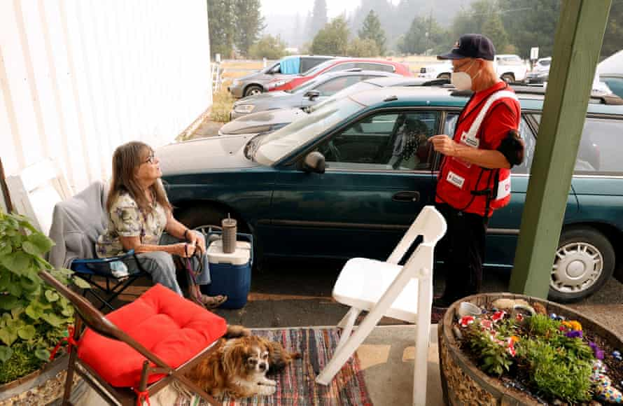 Marva Stewart, who has been evacuated from her home in Twain, California, talks Kevin Coster, a Red Cross volunteer, at a Dixie fire evacuation center in Quincy.