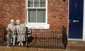 Statue of retired couple sitting on a bench in the front of a house in Ancoats Manchester.