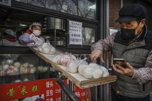 Beijing, China. A woman slides steam buns down a ramp used to avoid contact as a customer takes his order. The number of cases of Covid-19, a deadly new coronavirus, rose to more than 58,000 in mainland China