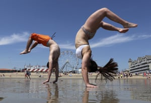 Maine, USDan and Alex two former high school cheerleaders, perform back flips while enjoying the record breaking heat, at Old Orchard Beach