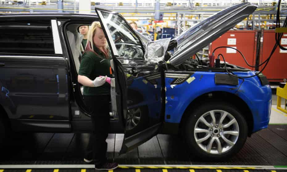 A Jaguar Land Rover worker inspects a vehicle in Solihull
