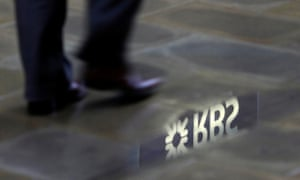 A man passes a puddle with the RBS logo reflected into it