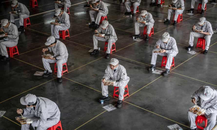 Workers eat a meal at a car factory in Wuhan in China's central Hubei province.