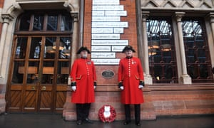 Chelsea pensioners next to the war memorial inside St Pancras International station.
