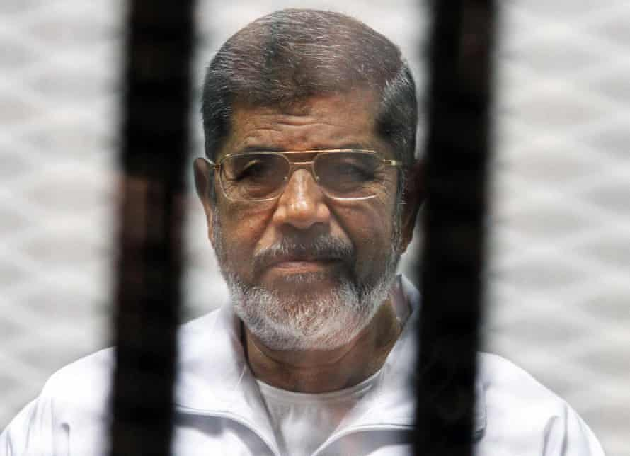 Egyptian ousted Islamist president Mohamed Morsi looking on from behind the defendants cage during his trial