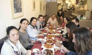 A large table full of diners at Quatre Amis restaurant in Paris.