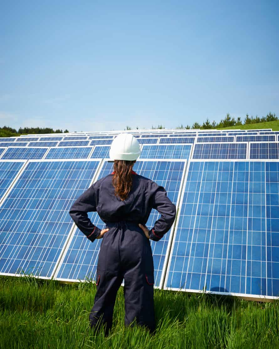 Female engineer looking at solar panel farm. Maintaining a photovoltaic power station.