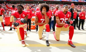 Colin Kaepernick, centre, and San Francisco 49ers team-mates Eli Harold, left, and Eric Reid kneel in protest against police brutality and oppression during the national anthem before last year's game against Dallas Cowboys.