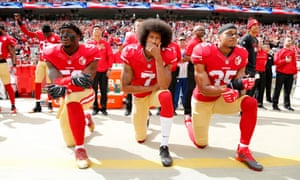 American football players Eli Harold, Colin Kaepernick and Eric Reid kneeling during the US national anthem to protest against police brutality