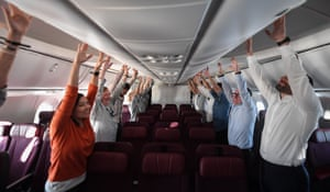 Passengers on a Qantas flight from London to Sydney take part in an exercise class
