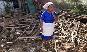 A women stands amid the ruins of her destroyed house in Comasagua, El Salvador, in January 2001, two days after an earthquake rocked Central America.