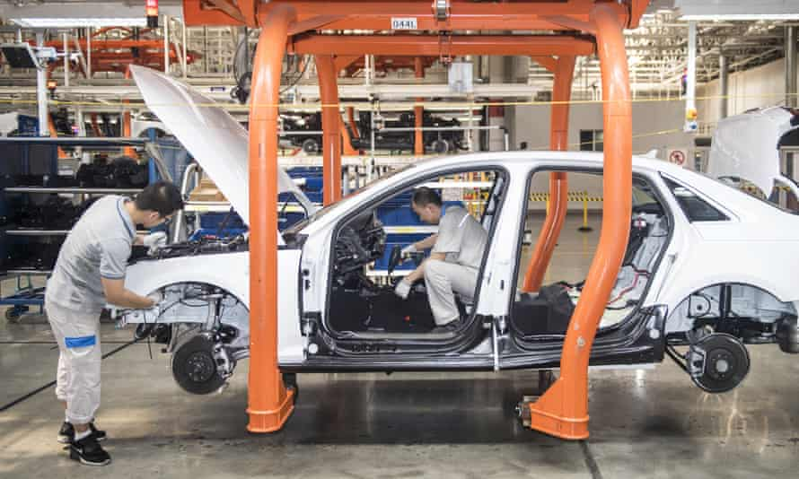 Workers assemble a car at an FAW-Volkwagen factory