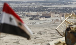 A Syrian flag flies over the ruins of Palmyra