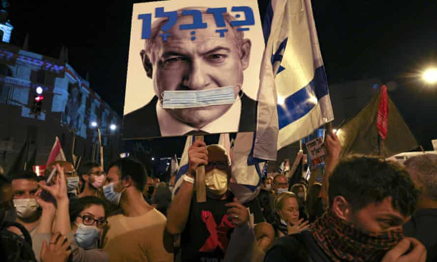 Protesters hold a poster of Benjamin Netanyahu