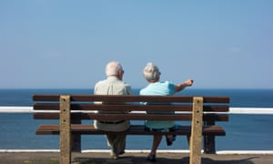 Retired couple sitting on bench by the sea