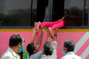 Secunderabad, India. Children are pushed through windows to board a bus as services resume after the government eased a nationwide lockdown