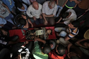 Palestinian mourners gather around the body of a man in Khan Yunis after he was killed during the protests at the Israel-Gaza border