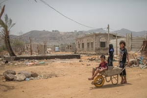 Youngsters play outside dilapidated homes in al-Buraiqeh district in Yemen