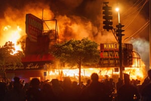 Protesters gather in front of a liquor store in flames near the Third Police Precinct