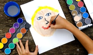 Child paints a face with water colours