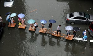 Wuhan residents cross a flooded street on a row of tables in 2012.