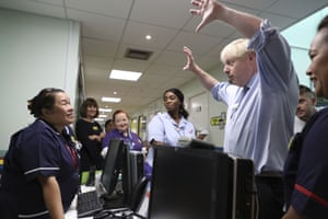 The prime minister, Boris Johnson, meets staff during a visit to Whipps Cross University Hospital, in London
